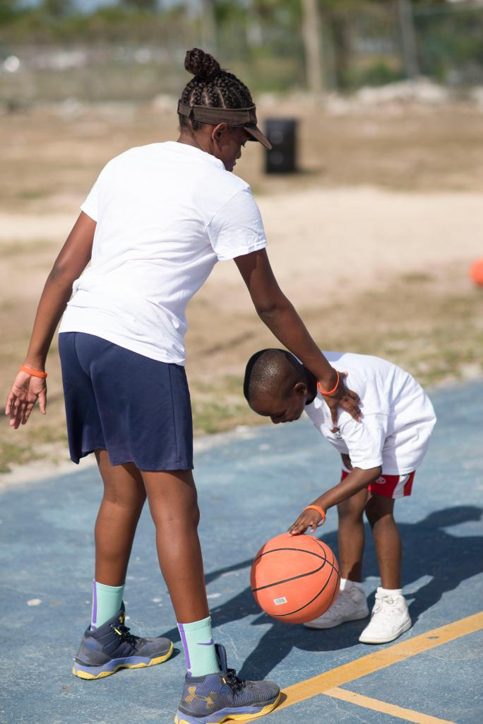 Older girl helps younger boy dribble a basketball