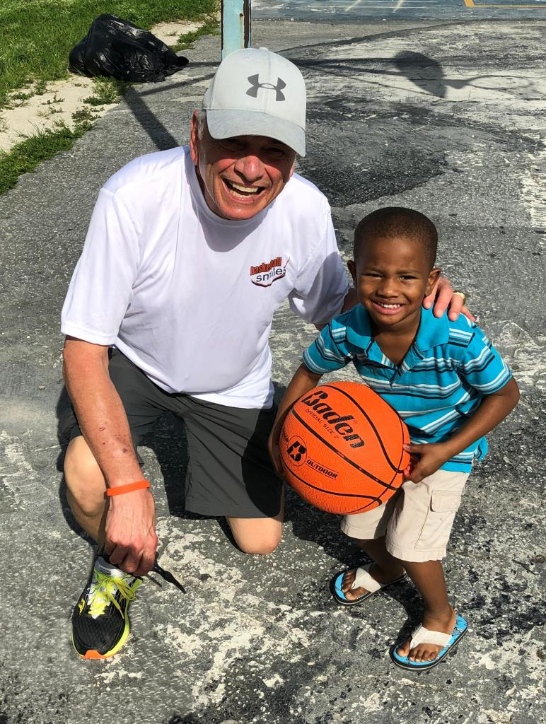 Coach Sam Nichols with little boy in flipflops
