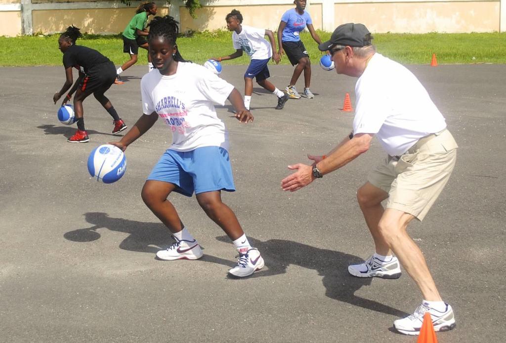 Coach Sam Nichols guards a girl with a basketball
