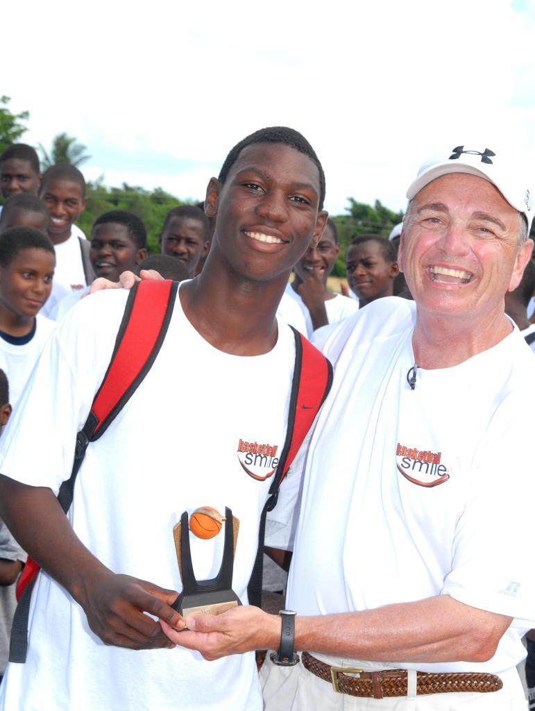 Coach Sam Nichols with trophy and older camper