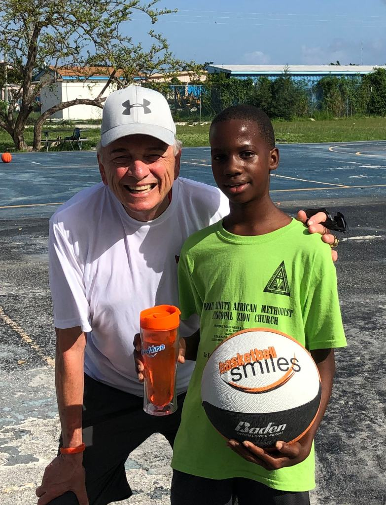 Coach Sam Nichols with camper holding a basketball