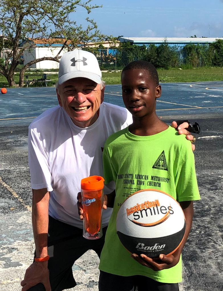 Coach Sam and camper with basketball