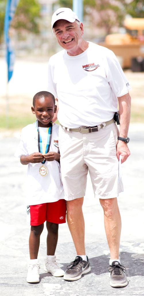 Coach Sam Nichols with boy wearing medal